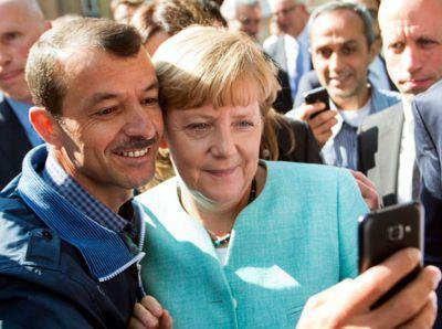 """Merkel forderte einen Schlaraffenland-Tramper auf, ein """"Selfie"""" mit ihr zu machen. Sie wollte, dass dieses Bild um die Welt geht, um Hunderte von Millionen zur Vernichtung der Deutschen anzulocken."""